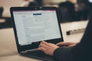 osoba pisząca artykuł na laptopie